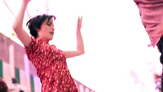 vídeos y material grabado en eventos de stock de young couple throw their hands in the air and spin under the bright lights of downtown las vegas - eufórico