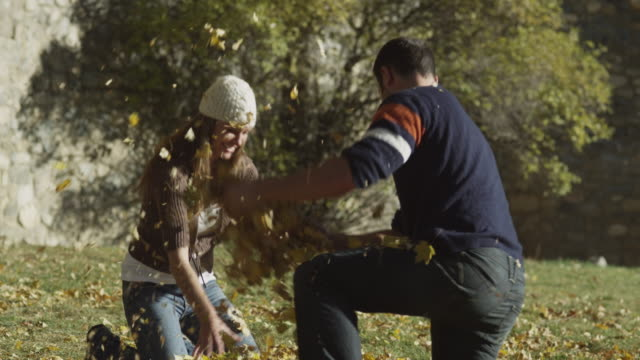 ms tu td young couple throwing leaves in park / provo, utah, usa - provo stock videos & royalty-free footage