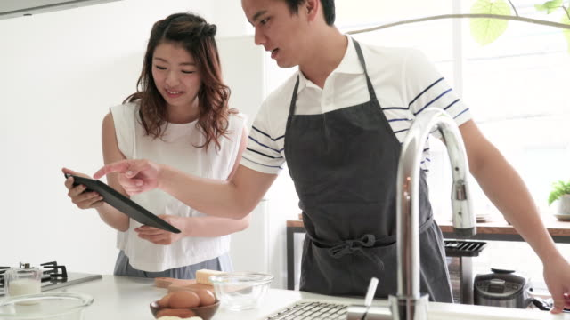 young couple to cook a look at the recipe - recipe stock videos & royalty-free footage