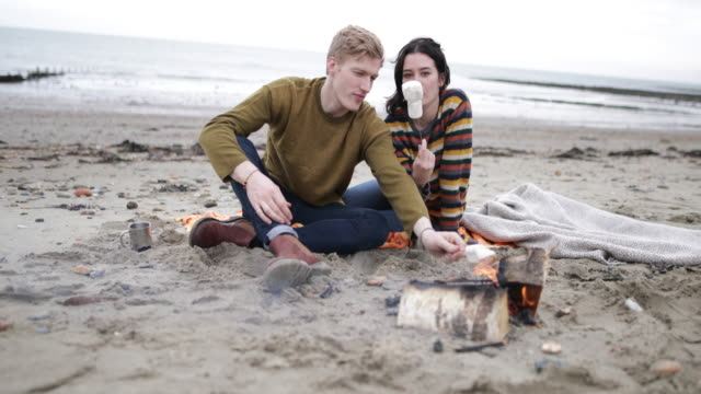 Young couple toasting marshmallows on camp fire