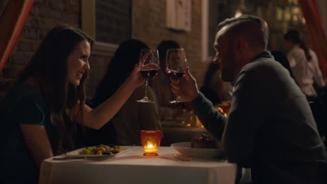 Young couple toasts and clinks wine glasses over dinner in romantic candlelit restaurant
