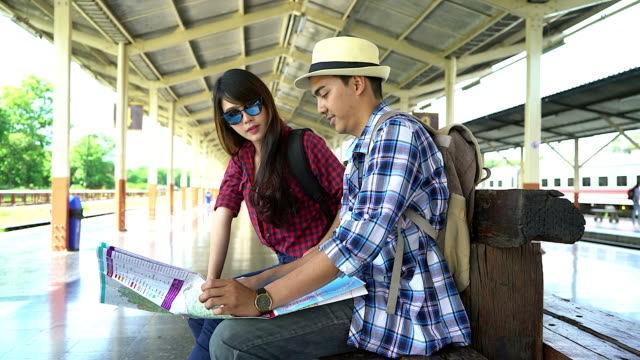 Young couple traveler looking map and discuss their trip at the train station.