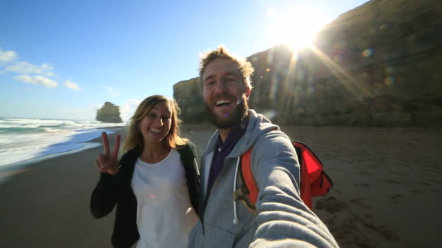 young couple traveling take selfie on beach - port campbell national park stock videos & royalty-free footage