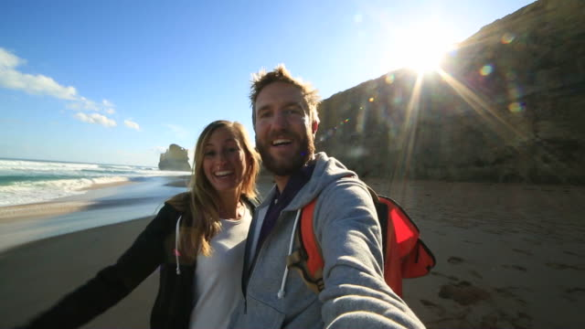 young couple traveling take selfie on beach - cliff stock videos & royalty-free footage
