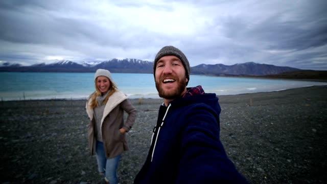 ungt par resor ta selfie porträtt av sjöstranden, nya zeeland - utsträckta armar bildbanksvideor och videomaterial från bakom kulisserna