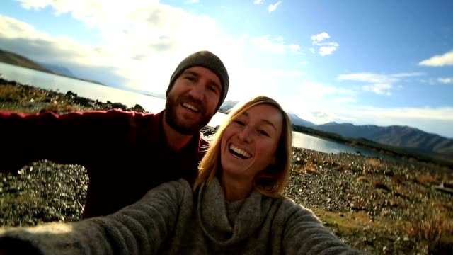 Young couple traveling take selfie portrait by the lake