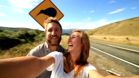 young couple traveling take selfie portrait with kiwi sign - road warning sign stock videos & royalty-free footage
