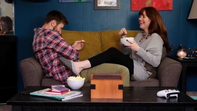vidéos et rushes de jeunes couples essayent d'attraper le pop-corn dans leur bouche - lockdown