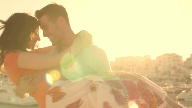 young couple twirling by marina in sunset. - 30 39 years stock videos & royalty-free footage