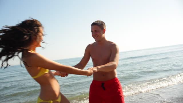 vídeos y material grabado en eventos de stock de young couple twirling on beach  - encuadre de tres cuartos
