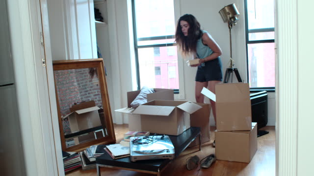 young couple unpacks boxes in new apartment - körperliche aktivität stock-videos und b-roll-filmmaterial