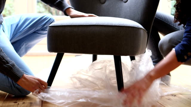 young couple unwrapping new chair in room - stol bildbanksvideor och videomaterial från bakom kulisserna