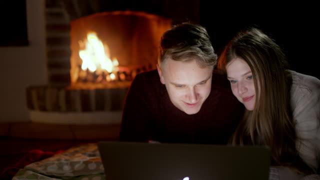 DS jeune couple à l'aide d'un ordinateur portable au coin du feu