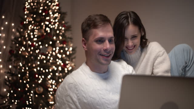 a young couple using a laptop congratulates their parents on christmas through a video call. - celebration event stock videos & royalty-free footage