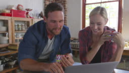 Young couple using a laptop in kitchen, close up, front view, shot on R3D