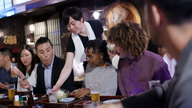 young couple using a mobile phone in a japanese izakaya - evening meal stock videos & royalty-free footage