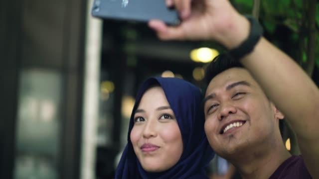 vídeos y material grabado en eventos de stock de pareja de jóvenes usando un teléfono móvil para tomar una selfie - pañuelo de cabeza