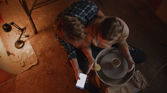 slo mo young couple using a smartphone while molding a clay in a pottery studio - pottery stock videos & royalty-free footage