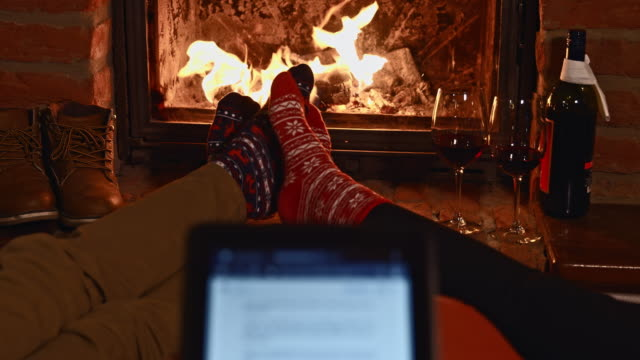 young couple using digital tablet by the fireplace - open fire stock videos & royalty-free footage