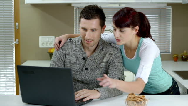 HD DOLLY: Young Couple Using Laptop At Home