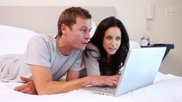couple using laptop on their bed - 中年カップル点の映像素材/bロール