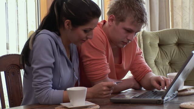 cu, young couple using laptop, woman holing credit card, ireland - holing stock videos & royalty-free footage