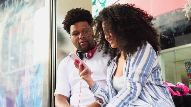 vídeos de stock, filmes e b-roll de casal jovem, usando o celular na rodoviária - casal jovem