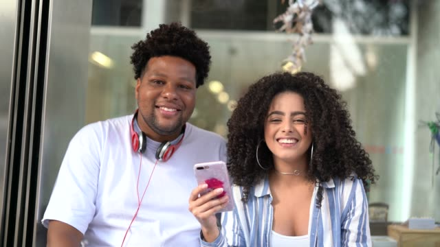 vídeos de stock, filmes e b-roll de casal jovem, usando o celular na rodoviária - ônibus