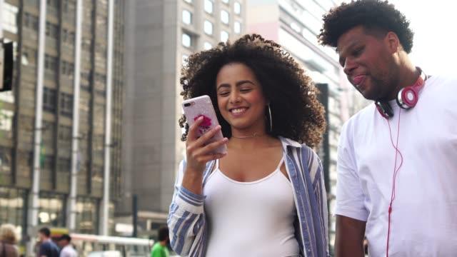 vídeos de stock, filmes e b-roll de jovem casal usando mobile ao ar livre - duas pessoas