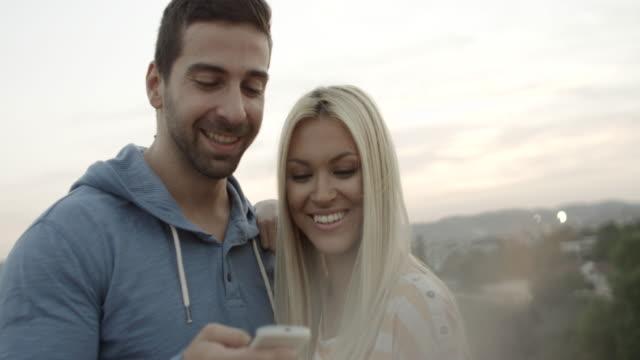 stockvideo's en b-roll-footage met jong stel met behulp van mobiele telefoon - ingesproken bericht