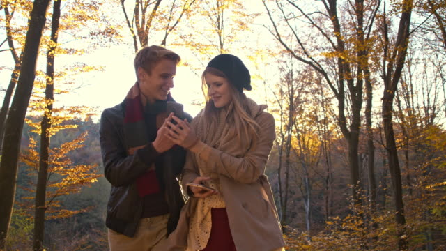 Young couple using mobile phones in autumn forest
