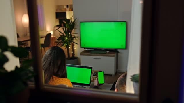 vidéos et rushes de couples jeunes de ds utilisant des dispositifs modernes avec les écrans verts de clé de chroma à la maison - image animée