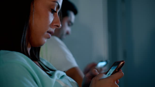 Young couple using smart phones in bed