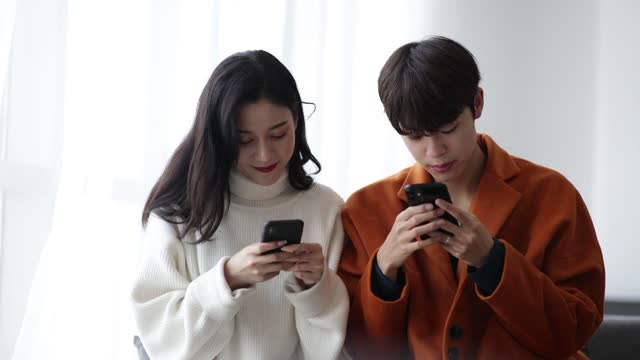 young couple using smartphone together - married stock videos & royalty-free footage