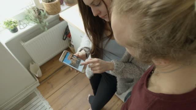 vídeos de stock, filmes e b-roll de young couple using smartphone - sobre os ombros