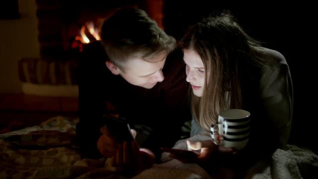 ds-junges paar mit smartphones am kamin in der nacht - hot kiss stock-videos und b-roll-filmmaterial