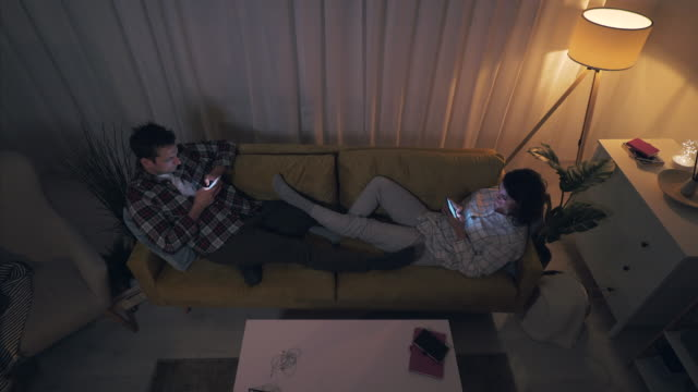young couple using smartphones late in night. - lying down stock videos & royalty-free footage