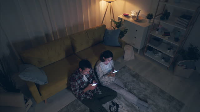 vídeos y material grabado en eventos de stock de pareja joven usando sus teléfonos móviles en casa. - adios