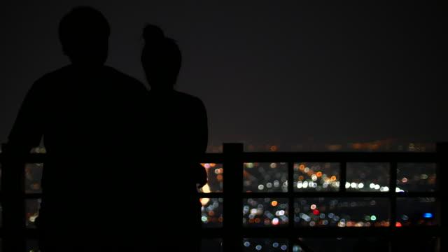 若いカップル背景にした表示星空の夜の都会の風景、4 k (uhd - 流星点の映像素材/bロール