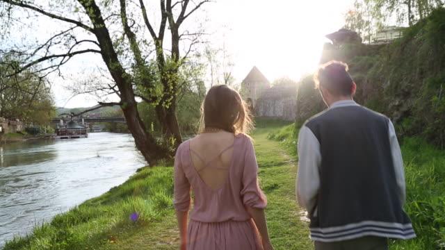 young couple walk along grassy riverbank, talking - bosnia and hercegovina stock videos & royalty-free footage