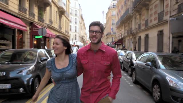 vidéos et rushes de young couple walk and talk down the rue de l'amiral hamelin in paris. - se garer