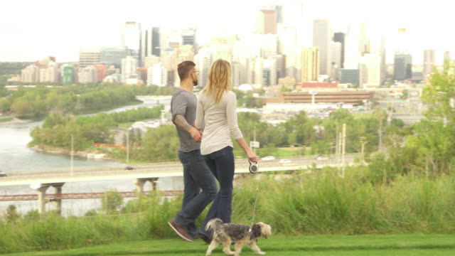 Young couple walk dog through city park, skyline behind