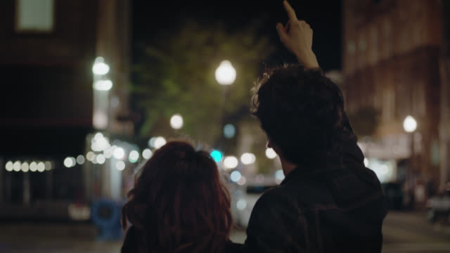 MS SLO MO. Young couple walk down city sidewalk and point up under twinkling streetlights.