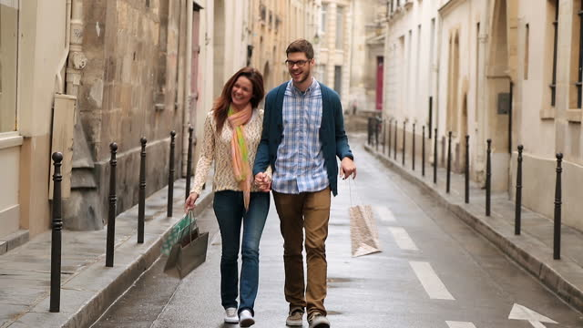 young couple walk hand in hand down paris side street with shopping bags and look in store window. - shopping bag stock videos & royalty-free footage