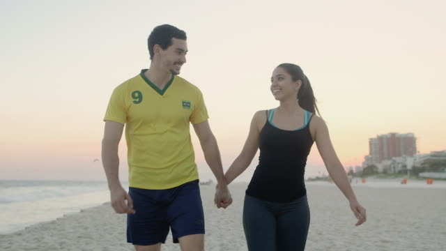 ms, ts a young couple walk on the beach at sunset / rio de janeiro, brazil - vest stock videos & royalty-free footage