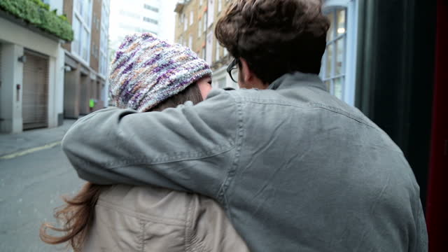 Young couple walk past colorful shopfronts and laugh on romantic stroll through London.
