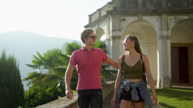 young couple walk through park overlooking lake and mountains - occhiali da sole video stock e b–roll