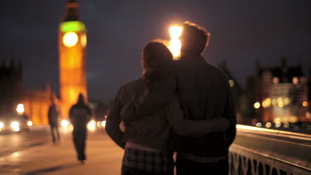 young couple walk together across westminster bridge at night. - big ben stock videos & royalty-free footage