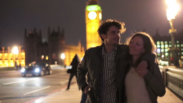 young couple walk together across westminster bridge towards the south bank at night. - date night romance stock videos and b-roll footage