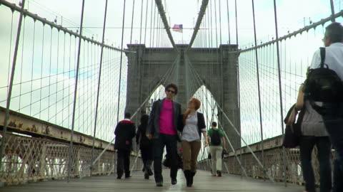 ws young couple walk toward camera on the brooklyn bridge/ new york city - hängbro bildbanksvideor och videomaterial från bakom kulisserna